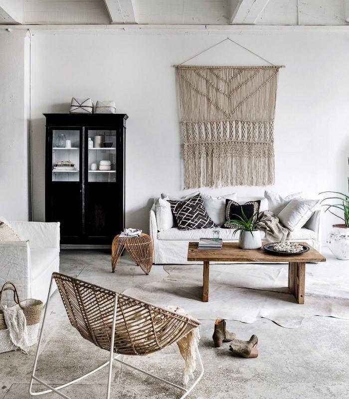 precioso salón decorado en blanco y negro en estilo minimalista con detalles decorativos de mimbre y madera y decoración macrame