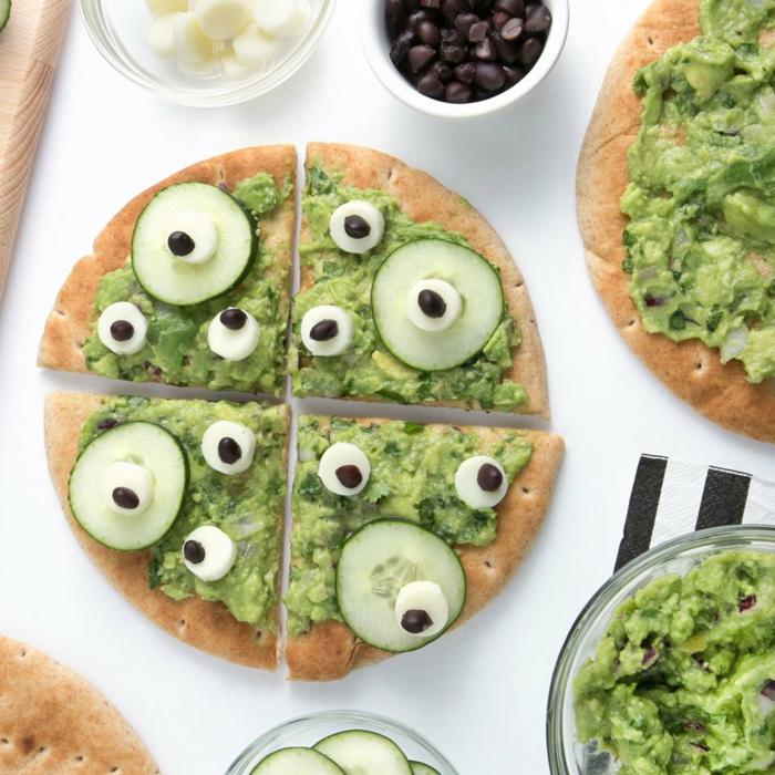 pizza casera con pasta de aguacate, yogur, pepinos y aceitunas negras, recetas de aperitivos halloween en 100 imagenes