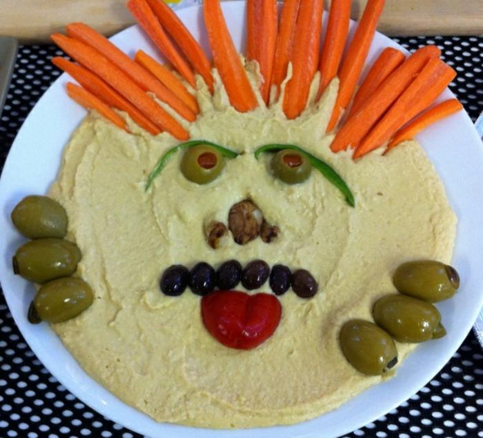 hummus casero decorado de manera original, aceitunas, pimiento rojo y zanahorias, recetas terrorificas para halloween