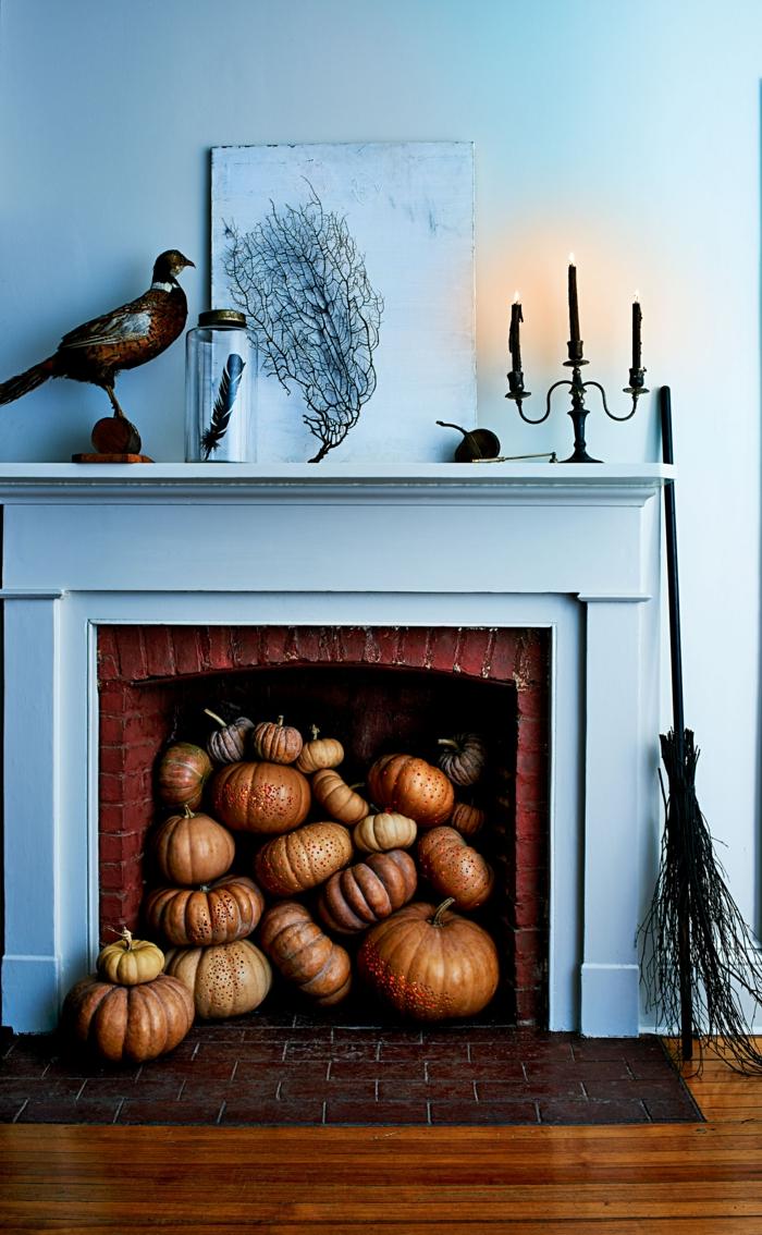 salón decorado en estilo rústico con paredes en color azul, chimenea llena de calabazas, candelabro vintage y elementos decorativos