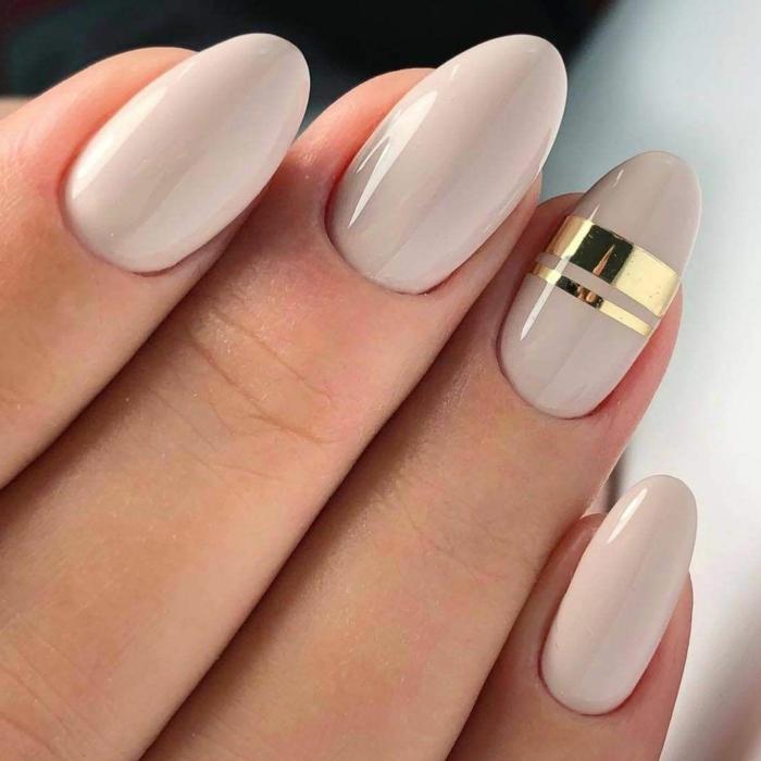uñas largas de forma almendrada pintadas en beige con detalles decorativos en dorado, uñas de gel colores modernos