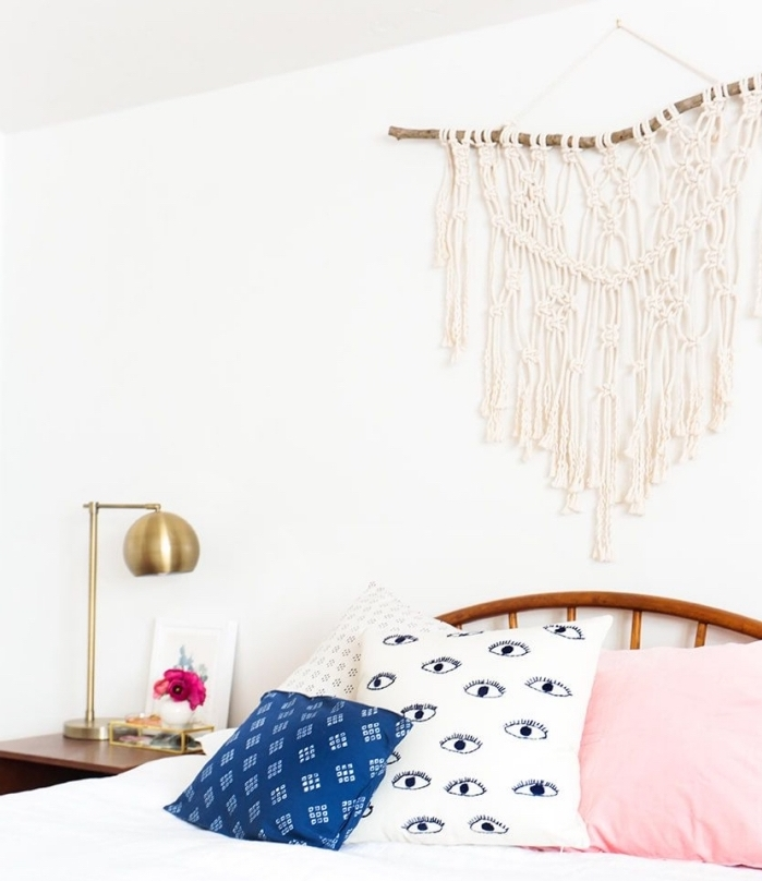 decoración dormitorio en color blanco con elementos en estilo boho chic, cama de madera con cabecero y colgante macrame