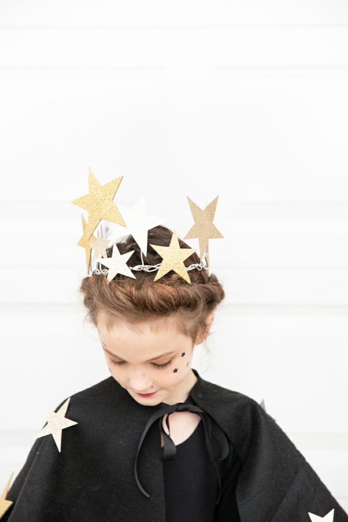 preciosa idea para un disfrace niña, corona de estrellas de cartón en dorado, capa negra de fieltro adornada con estrellas