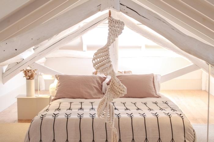 precioso dormitorio con techo inclinado decorado en blanco, suelo de parquet y techo de vidas, cama doble, decoración en tonos claros