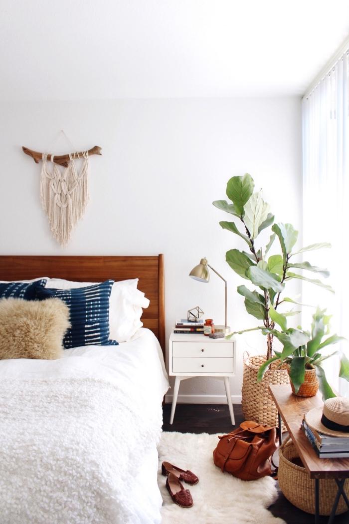 dormitorio matrimonio acogedor decorado en blanco con plantas verdes, cama doble con cabecero de madera y objetos decorativos