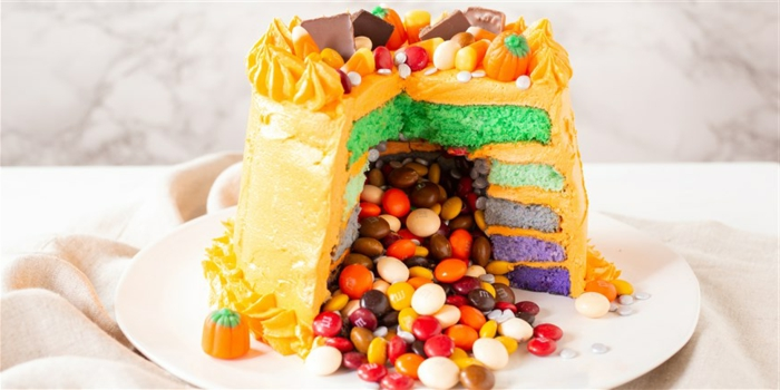 tarta sorpresa llena de caramelos coloridos, recetas divertidas para Halloween, más de 100 ideas de recetas para el otoño