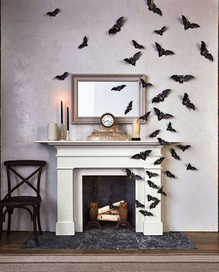 salón decorado en estilo rústico con chimenea de leña, decoración con murciélagos de papel, decoracion halloween casera