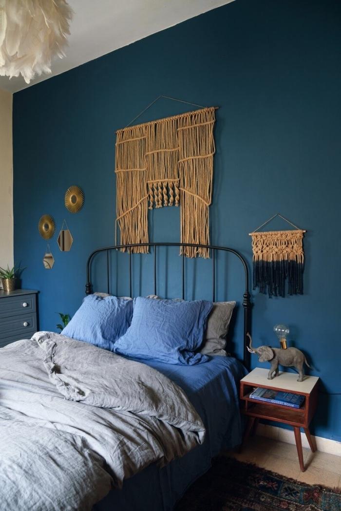 dormitorio decorado en estilo boho chic con paredes en azul intenso, cama doble con cabecero y detalles decorativos en la pared