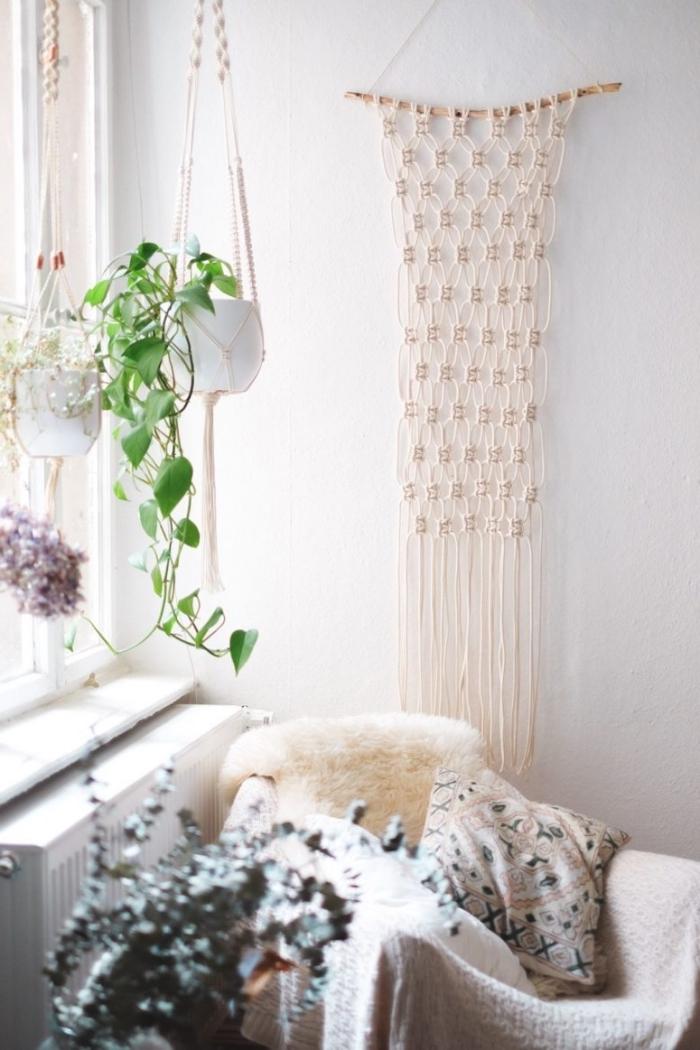 precioso detalle decorativo de macrame en la pared, espacio decorado en blanco con plantas verdes y muebles en colores claros