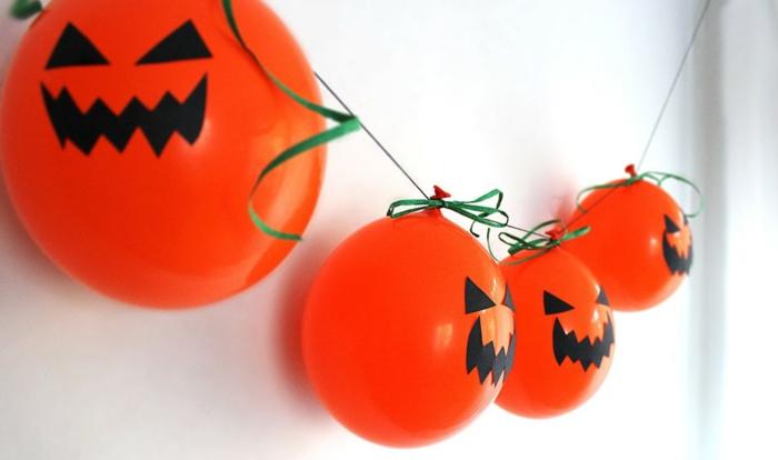 globos en color naranja decorados con fieltro color negro, manualidades de halloween para niños, originales ideas en fotos