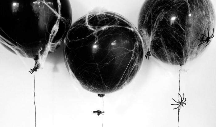 decoracion con globos para montar una fiesta de Halloween, globos negros, pequeñas arañas de plástico y algodon