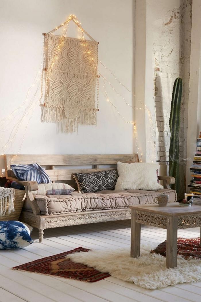 pequeño salón decorado en estilo boho chic con decoración en la pared, sofá en estilo rústico y muebles de madera