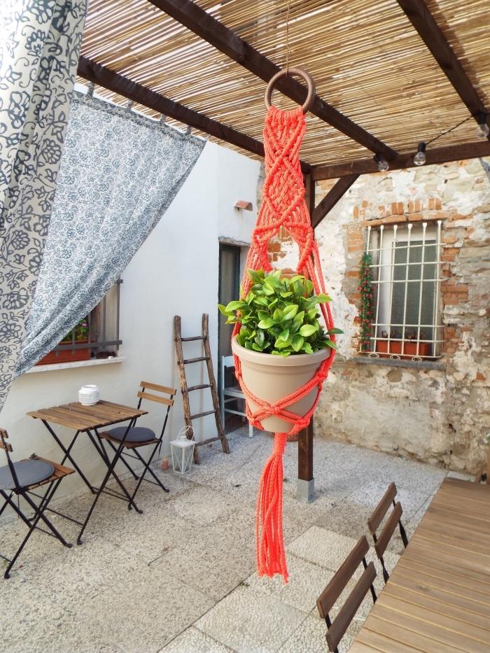 jardín decorado en estilo rústico con bonito colgante macrame color naranja, ideas de decoración de terrazas y espacios abiertos