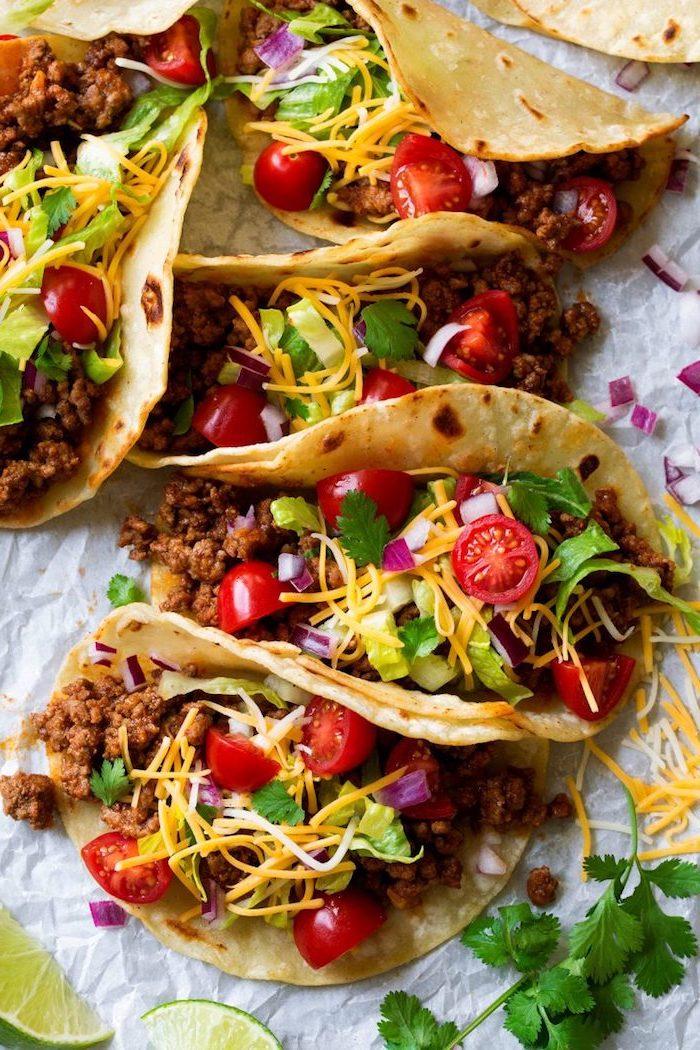 tacos con carne picada, queso cheddar rallado, tomates cereza cortados a la mitad y perejil fresco, fotos de tacos