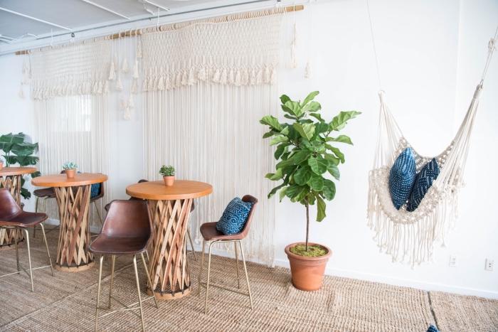 grande salón decorado en estilo bohemio con plantas verdes y cortinas de macrame, cortina de macrame y silla colgante