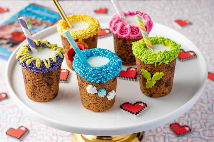 postres originales y coloridos para una fiesta infantil, tazas llenas de leche hechas de masa para galletas