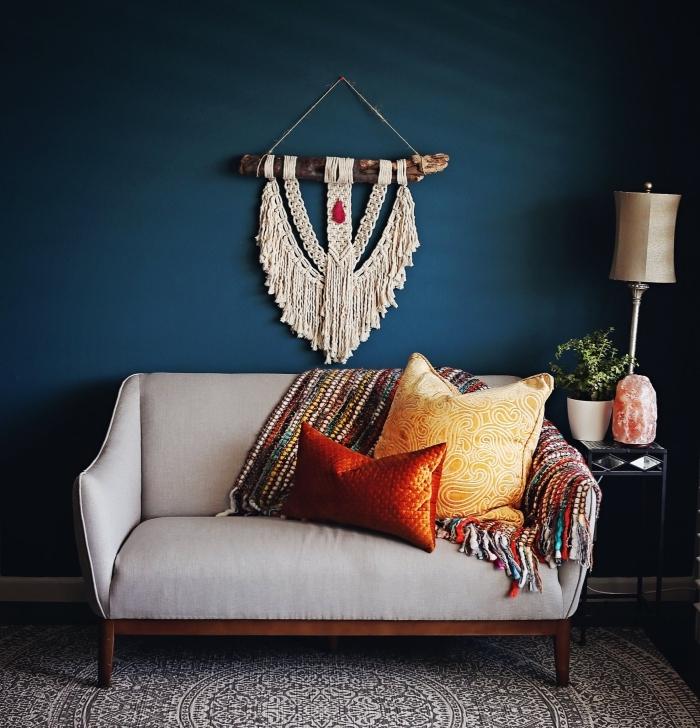 salón decorado en estilo bohemio con detalles étnicos, sofá pequeña en color gris y cojines en colores vibrantes, decoración en la pared
