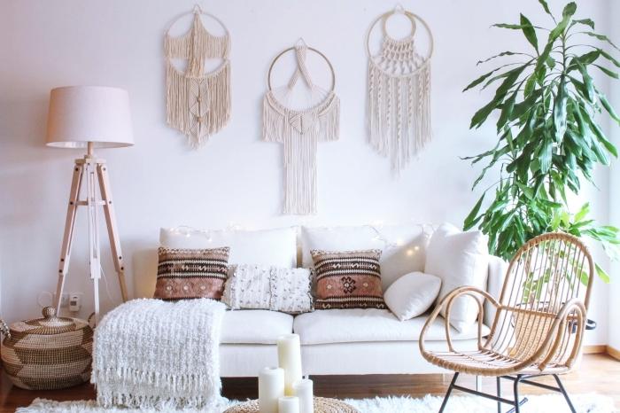 cortinas macrame y colgantes decorativos para la pared, salón decorado en color blanco con sofá blanca y cojines ornamentados etno