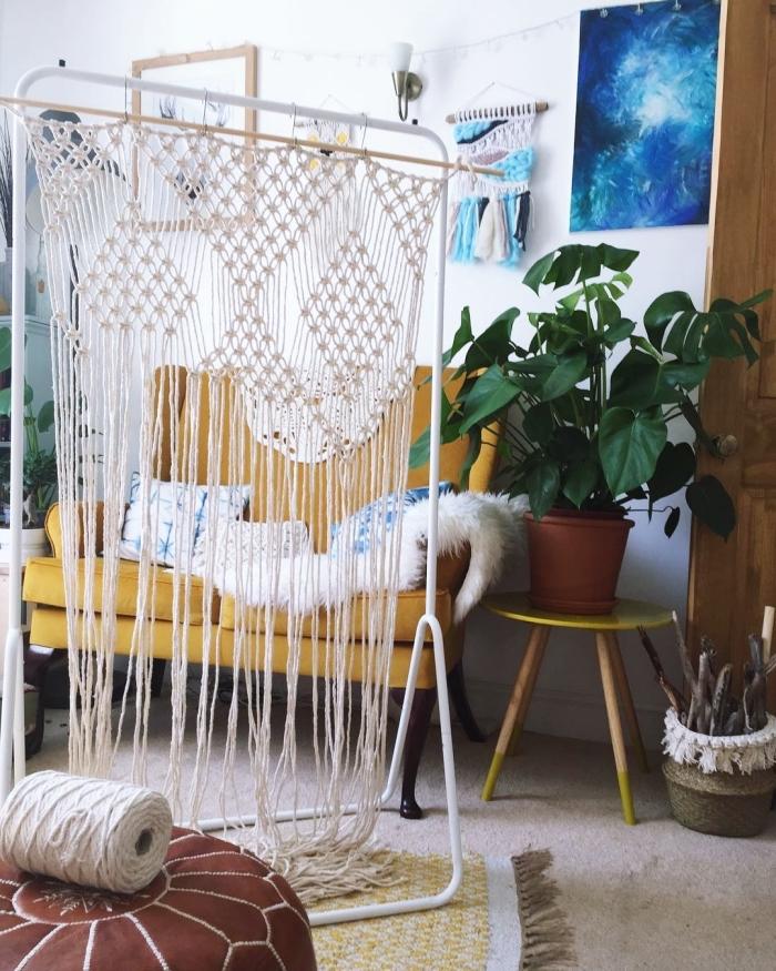 salón pequeño decorado en estilo boho chic con cortina macrame y cuadros decorativos en la pared, decoración salón ideas