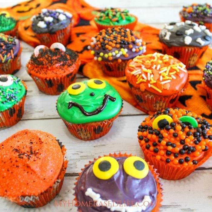 magdalenas Halloween coloridas con palitos de azúcar y decoración en los colores de la fiesta, postres de Halloween caseros