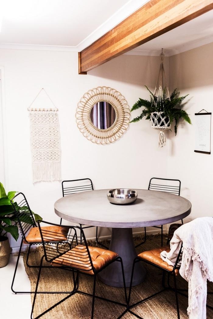 salón comedor decorado en estilo vintage con objetos estilo bohemio, espejo vintage en la pared y plantas verdes