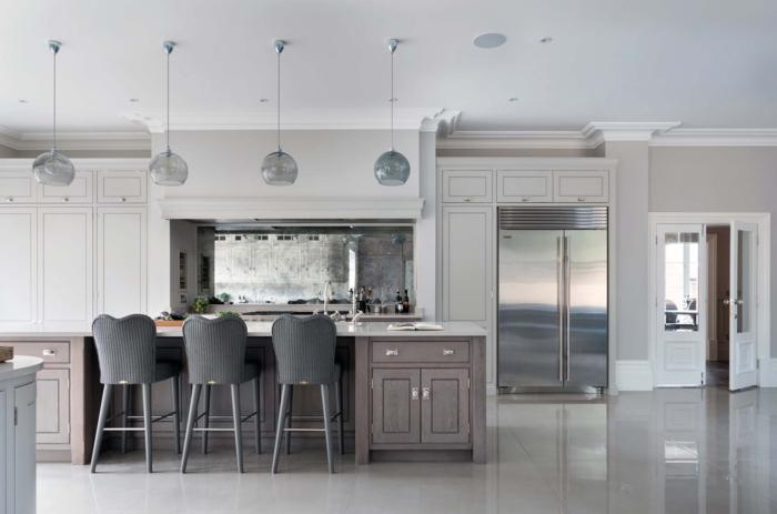 grande cocina integrada en salón, paredes blancas, lámparas colgantes modernas, muebles en tonos de beige y gris
