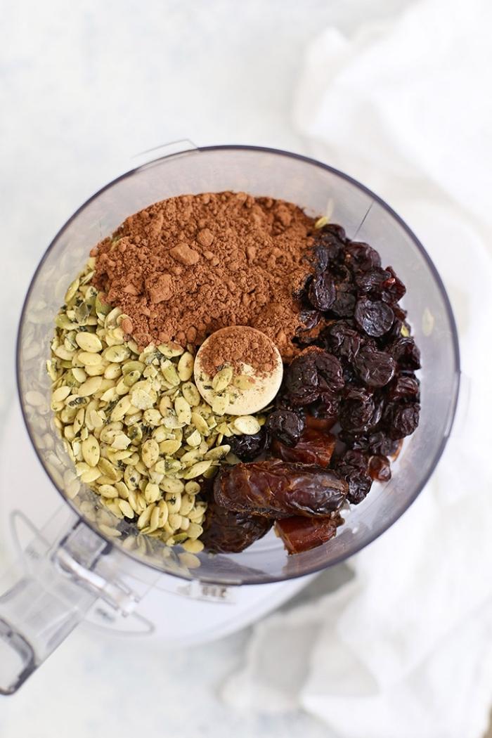 ingredientes para hacer bocados energéticos saludables en un procesador de alimentos, semillas de calabaza cacao en polvo, frutas secas