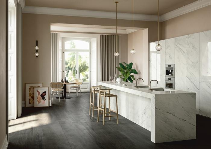 últimas tendencias en decoracion de cocinas, cocina blanco y beige con suelo de parquet y grande barra de mármol
