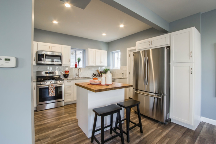 cocina americana en color azul y blanco con suelo de parquet, luces empotradas en el techo, armarios pintados en blanco