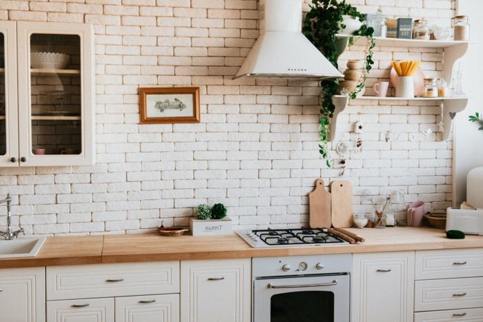 espacio decorado en color blanco y beige, pared decorada con ladrillos, barra de cocina con encimera imitación de madera