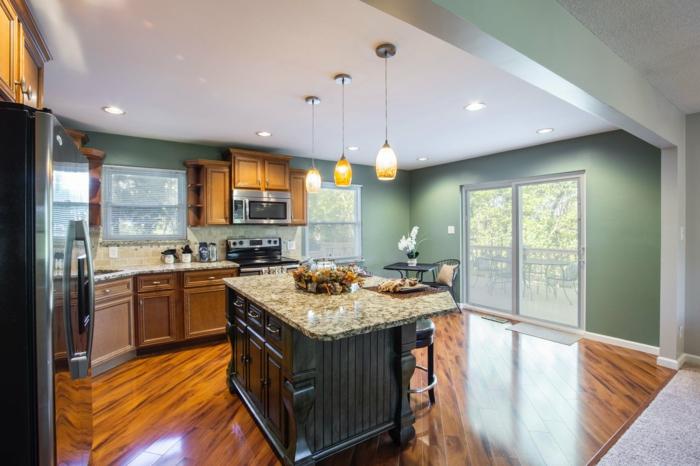 ejemplos sobre barra americana cocina, barra con encimera en beige y negro y sillas altas negras, cocinas grandes modernas