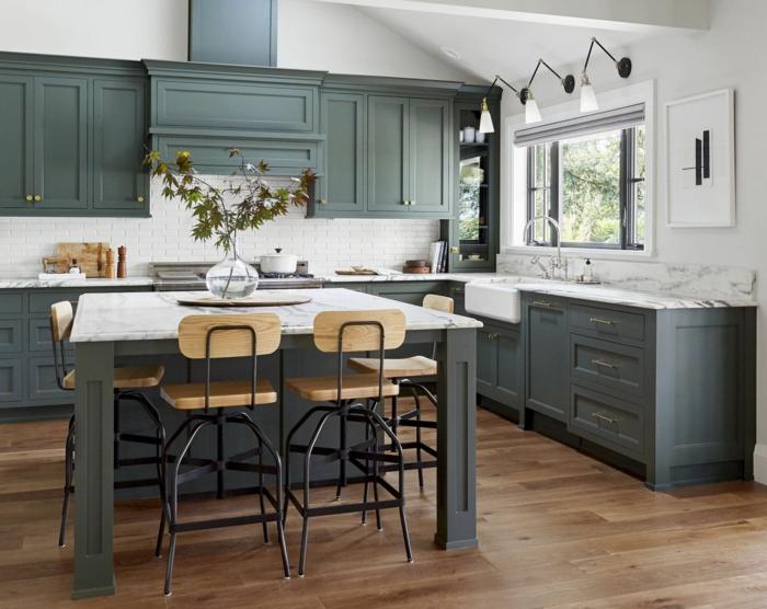 cómo amueblar una cocina con grande barra, sillas altas con asientos de madera, encimara de mármol, armarios en gris