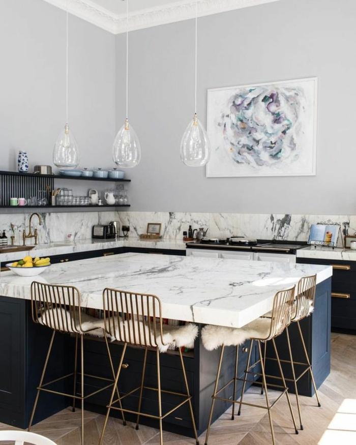 cocina decorada en colores claros con muebles de mármol y cuadros decorativos, lámparas colgantes de diseño