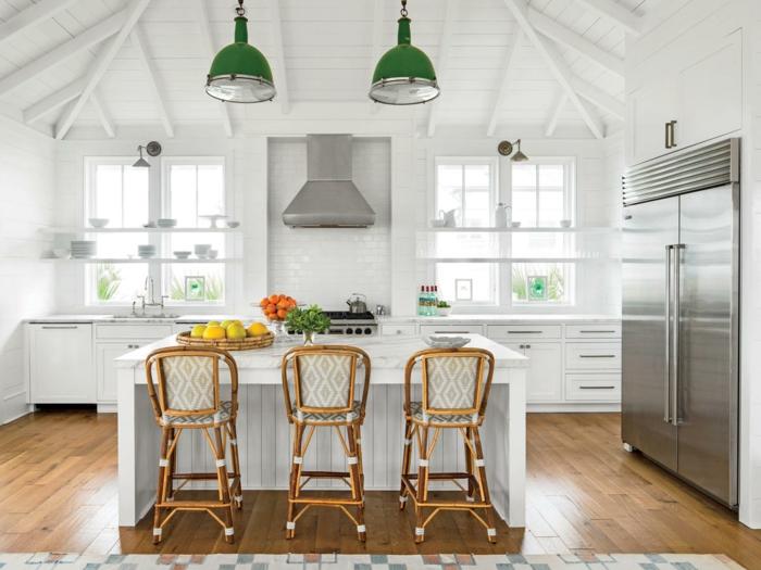 cocina en blanco con grande barra y sillas altas, suelo de parquet y techo con vigas, espacio decorado en estilo industrial