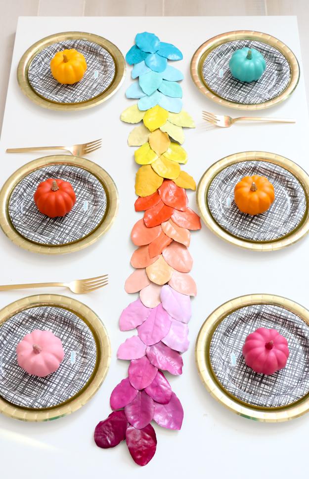 coloridas ideas sobre como vestir la casa en otoño, centro de mesa con hojas de otoño pintadas en los colores del arco iris