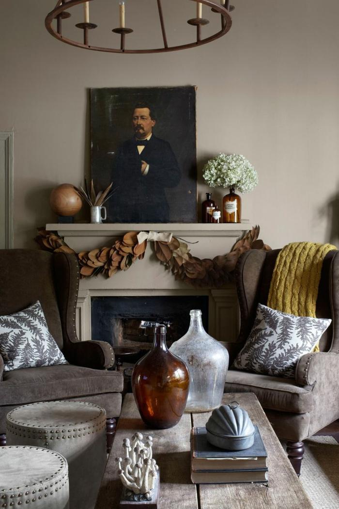 salón decorado en estilo rústico, chimenea de leña con guirnalda de flores de otoño, mesa de madera y sillones en estilo vinage