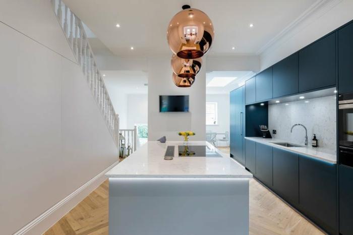 cocina con grande peninsula, lámparas en color rosa dorado, barra multifuncional con encimera en blanco, salon cocina americana