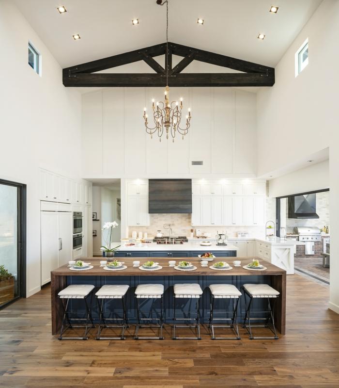 barra grande con sillas altas blancas, cocina abierta al salón, cocina techo alto con luces empotradas, techo con vigas