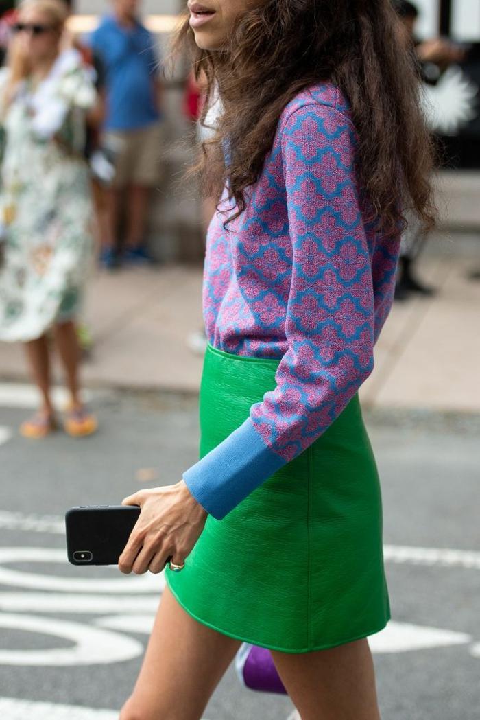 falda de cuero corta en color verde vívido, blusa en color lila y azul con motivos florales, ideas de colores en tendencia moda mujer