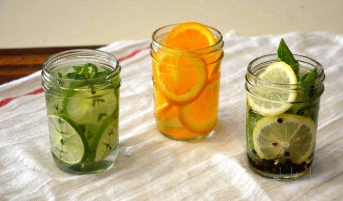 frascos de vidrio llenos de ingredientes naturales para aromatizar la casa en verano, ambientadores cítricos caseros
