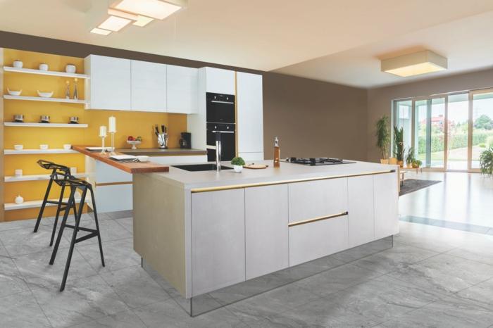 precioso diseño de cocina con barra multifuncional, cocinas abiertas al salon, pared en color amarillo con estanterias