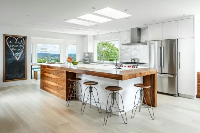 cocina decorada en estilo rústico moderno con pizzara negra en la pared, grande barra con sillas altas y suelo de parquet