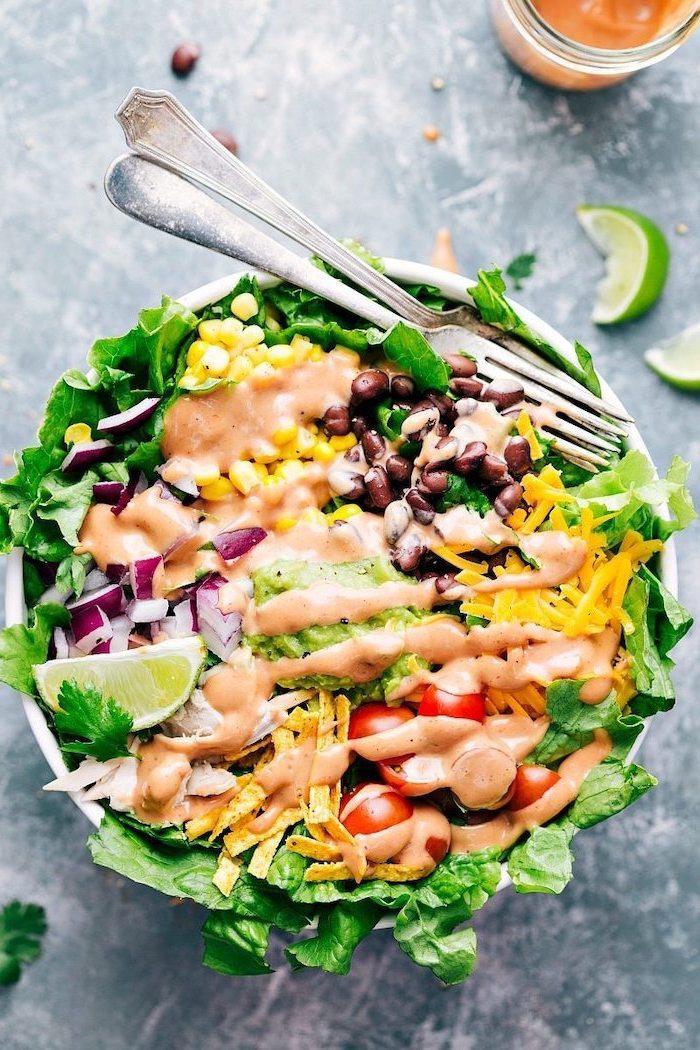 ensalada con salsa cremosa, lima, lechuga, queso rallado, perejil y cebolla roja, ensaladas para cenar ricas y fáciles de hacer