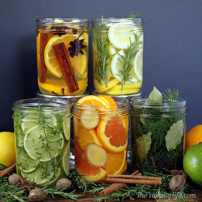 frascos de vidrio llenos de trozos de lima y naranja y palos de canela, ideas sobre como hacer que tu casa huela a Navidad