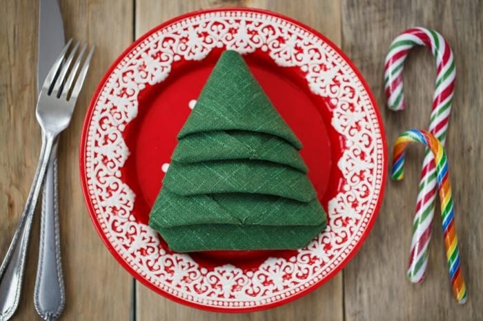 ideas sobre cómo doblar servilletas de manera encantadora para una cena de Navidad, servilleta de tela color verde y plato rojo