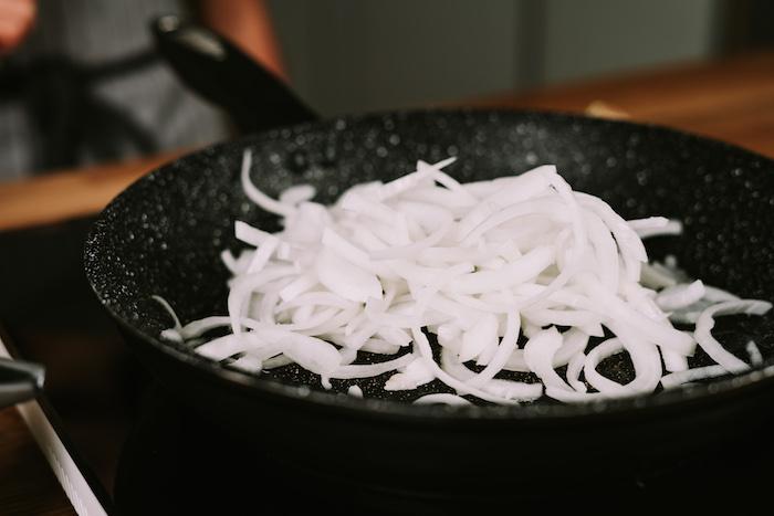pasos para hacer crema de calabaza, freir cebolla blanca en una sartén, ideas para hacer receta de sopa casera para el invierno