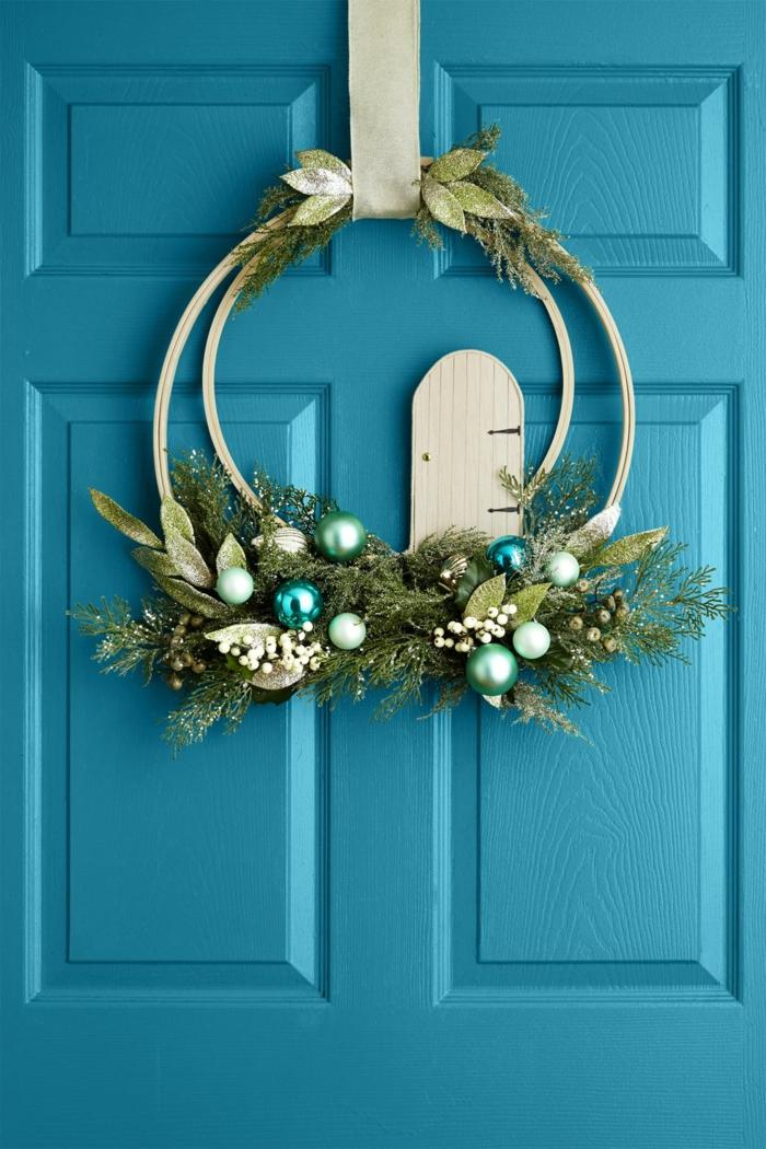puerta pintada en azul con bonito adorno con ornamentos pequeños en los tonos del verde, decoración clásica para Navidad