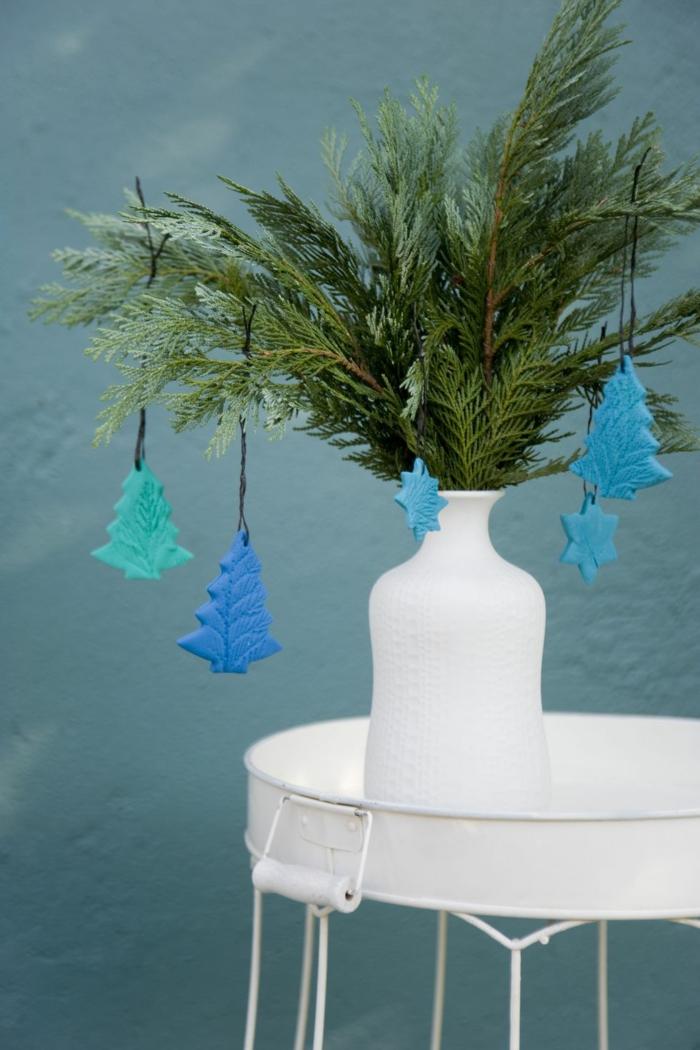 decoracion casera con ramas de pino, florero blanco en una mesa blanca estilo minimalista, pequeños adornos de arcilla en color azul