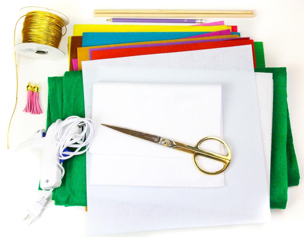 materiales necesarios para hacer un árbol navieño de fieltro, pistola de pegamento caliente, hilo en dorado, hojas de fieltro