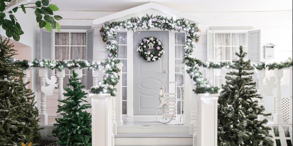 ideas sobre como decorar el porche en Navidad, decoración en blanco y gris y guirnalda verde con bolas en lila y blanco